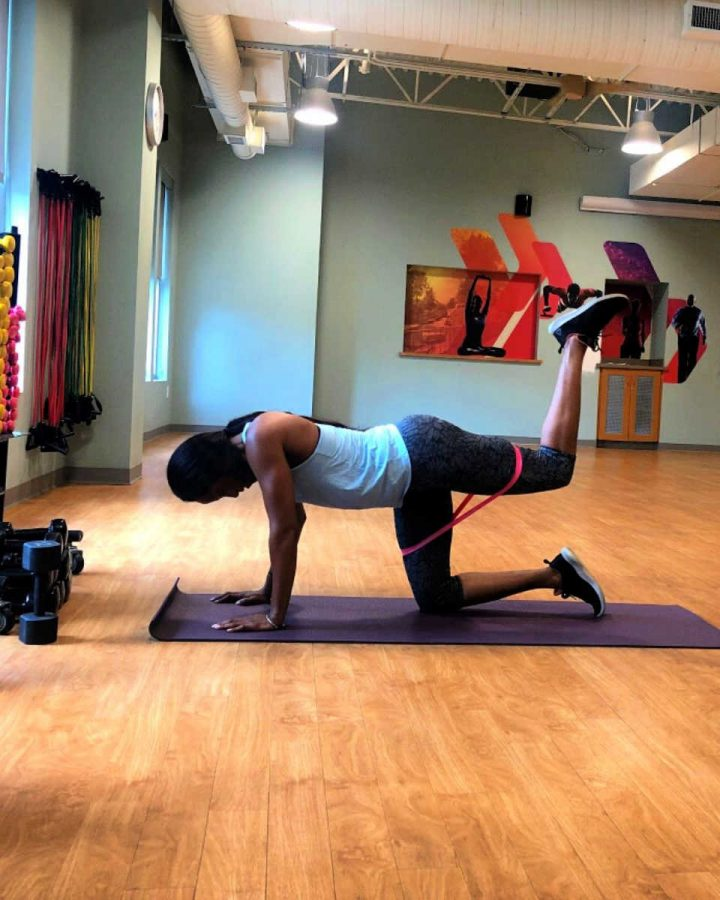 woman on floor doing glute and hamstrings lower body resistance band workout