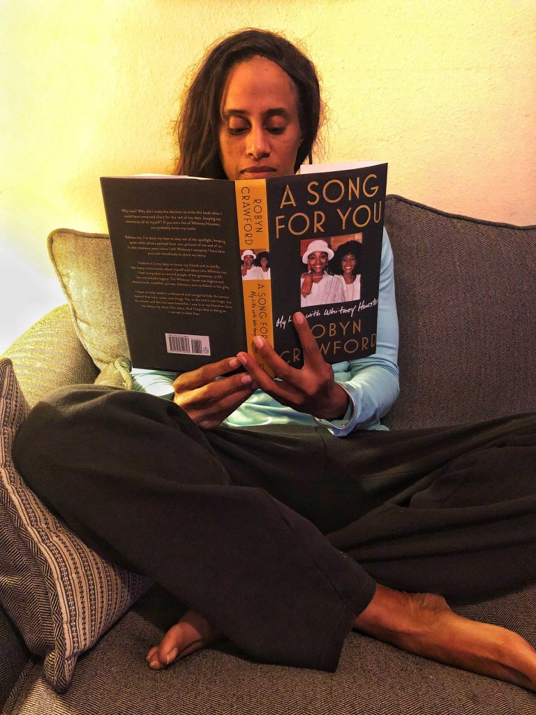 a woman reading A Song for You by Robyn Crawford on the sofa