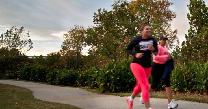 women running together on sidewalk